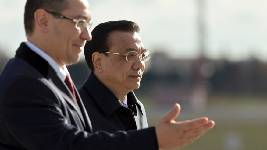 China's Premier Li Keqiang, right, walks alongside the Prime Minister of Romania Victor Ponta, upon arriving at the Henri Coanda airport, outside Bucharest, Romania, Monday, Nov. 25, 2013. China's Premier will attend the China - Central and Eastern Europe meeting of heads of government, starting Tuesday in the Romanian capital. (AP Photo/Vadim Ghirda)
