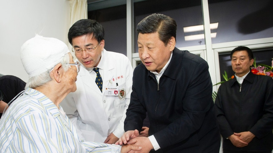 In this photo released by China's Xinhua News Agency, Chinese President Xi Jinping, center, visits a patient injured in deadly explosions that ripped through residential and commercial roads from a ruptured pipeline owned by the country's largest oil refiner,  at the Huangdao branch of the hospital affiliated with the Medical College of Qingdao University in Qingdao, a coastal city in east China's Shandong Province, Sunday, Nov. 24, 2013. Dozens were killed in Friday's industrial accident in eastern China and rescue efforts were continuing.  The accident was the deadliest involving state-owned company Sinopec. (AP Photo/Xinhua, Huang Jingwen)