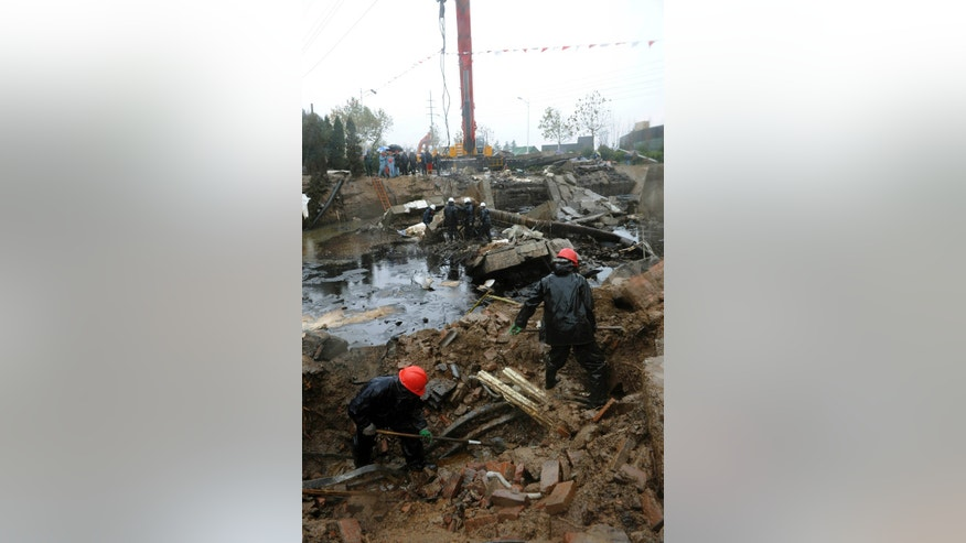 In this photo released by China's Xinhua News Agency, workers dig through rubble at the site of a pipeline explosion in Qingdao Development Zone, in Qingdao, east China's Shandong Province, Sunday, Nov. 24, 2013. Deadly explosions ripped through residential and commercial roads from a ruptured pipeline owned by the country's largest oil refiner on Friday, killing dozens. At least 10 people were still missing, according to the information office of the government of the port city of Qingdao, and rescue efforts were continuing. The accident was the deadliest involving state-owned company Sinopec.  (AP Photo/Xinhua, Li Ziheng)