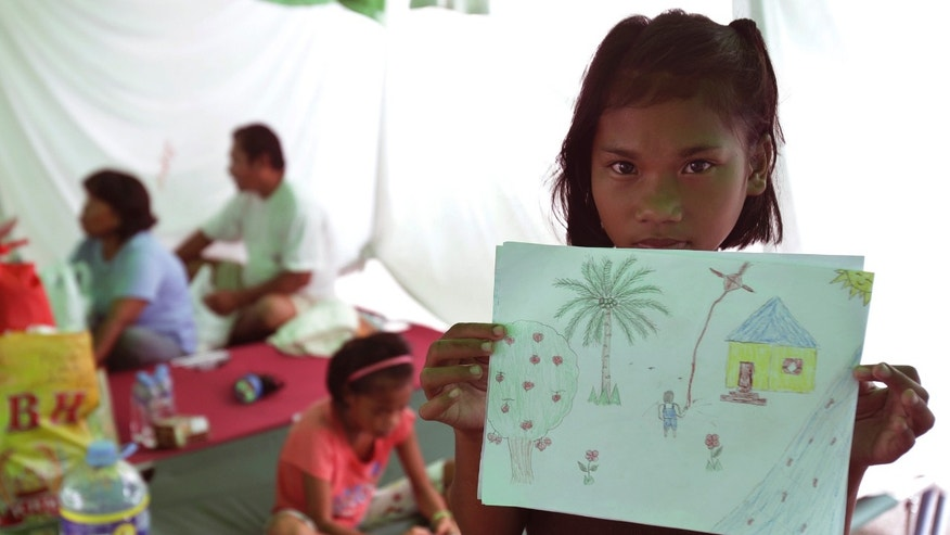"In this  Friday Nov. 22, 2013 photo, typhoon survivor Jennifer Dawat, 13, poses a photo with her crayon drawing of the family's happier days in Leyte's Ormoc city, at a temporary shelter in Pasay city, south of Manila, Philippines. The drawing showed a girl flying a kite beside a box-like yellow house with a blue roof and a coconut tree, and a smiling yellow sun overhead. ""That's our house,"" she said. ""It's gone.""  (AP Photo/Aaron Favila)"
