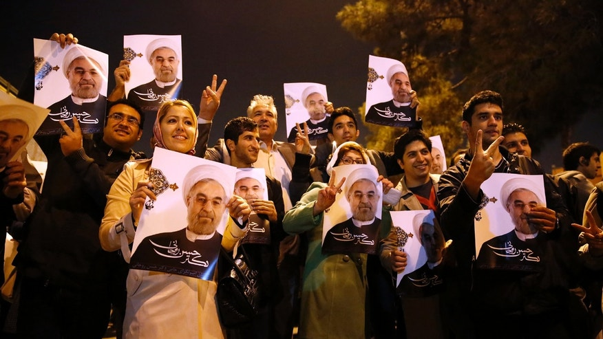 In this photo released by the Iranian Students News Agency, ISNA, Iranians hold posters of President Hassan Rouhani as they welcome Iranian nuclear negotiators upon their arrival from Geneva at the Mehrabad airport in Tehran, Iran, Sunday, Nov. 24, 2013. Hundreds of cheering supporters greeted Iran's nuclear negotiators as they arrived back to Tehran late Sunday night. Tehran agreed Sunday to a six-month pause of its nuclear program while diplomats continue talks. International observers are set to monitor Iran's nuclear sites as the West eases about $7 billion of the economic sanctions crippling the Islamic Republic. (AP Photo/ISNA,Hemmat Khahi)