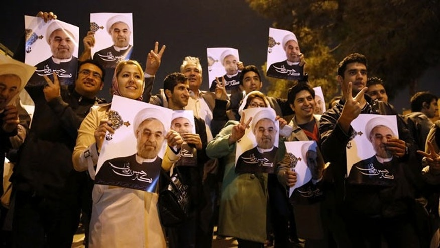 November 24, 2013: In this photo released by the Iranian Students News Agency, ISNA, Iranians hold posters of President Hassan Rouhani as they welcome Iranian nuclear negotiators upon their arrival from Geneva at the Mehrabad airport in Tehran. (AP Photo/ISNA)