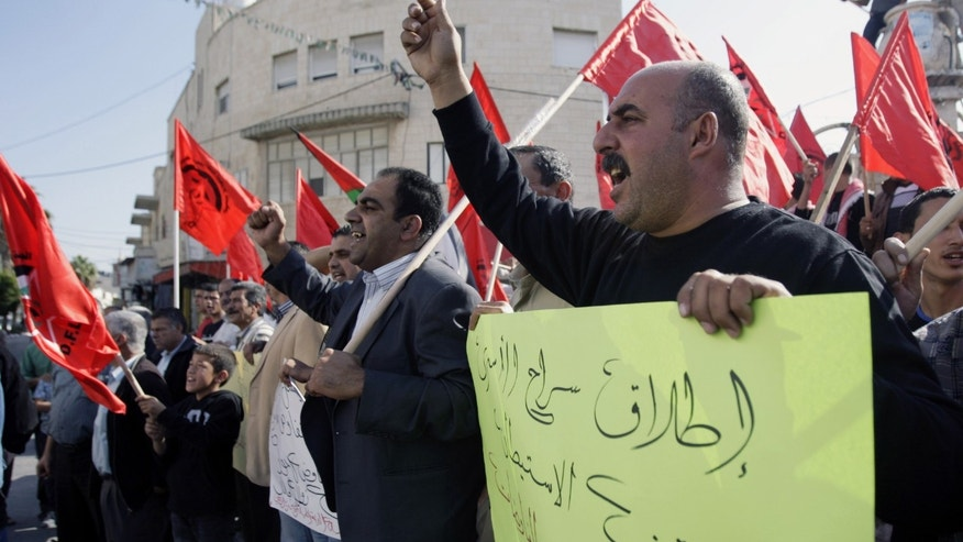 "Members of the Democratic Front for the Liberation of Palestine chant slogans against peace negotiations with Israeli, while participating in a demonstration in the West Bank city of Jenin, Thursday, Nov. 21, 2013. The Arabic, front, reads, ""Release prisoners and stopping the settlement is the basis to start negotiations."" (AP Photo/Mohammed Ballas)"