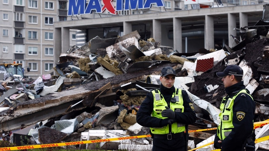 Policemen stand near a collapsed Maxima supermarket in Riga, Latvia, Sunday, Nov. 24, 2013. A massive third section of the roof at the supermarket where scores of people were killed fell as emergency workers searched nearby rubble for more victims. Investigators are looking at faulty construction or work on the roof's grass and gravel covered surface as the potential cause of the initial collapse in the crowded supermarket on Thursday. (AP Photo/Mindaugas Kulbis)