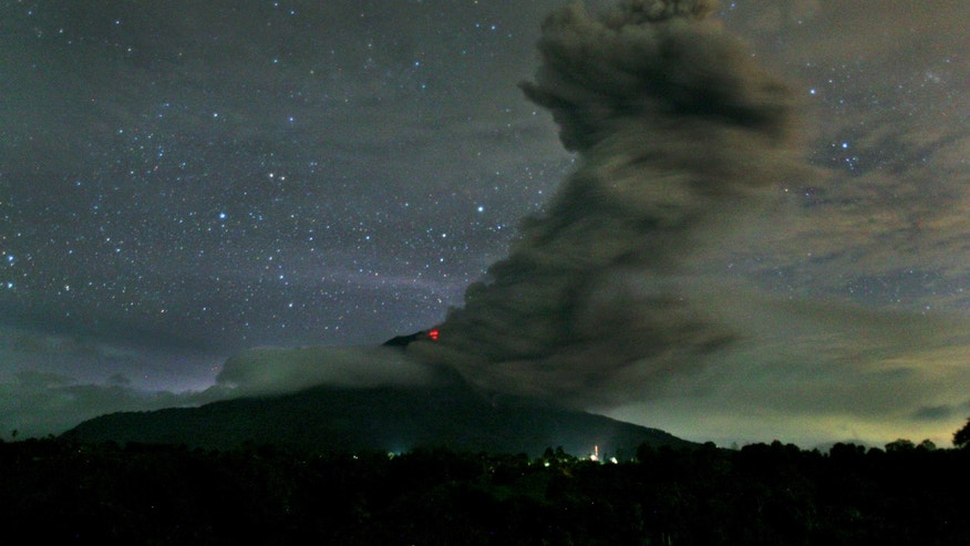 In this late Sunday, Nov. 24, 2013 photo, Mount Sinabung spews volcanic ash into the air as seen from Tiga Pancur, North Sumatra, Indonesia. Authorities raised the alert status for one of the country's most active volcanoes to the highest level Sunday after the mountain repeatedly sent hot clouds of gas down its slope following a series of eruptions in recent days. (AP Photo/Binsar Bakkara)