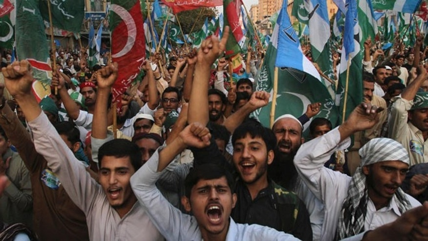 Nov. 24, 2013: Supporters of the Pakistani religious party Jammat-e-Islami and Tehreek-e-Insaf party, headed by cricketer-turned politician Imran Khan, hold up their parties' flags and chant slogans during a rally against U.S. drone strikes in Pakistani areas, in Karachi, Pakistan.