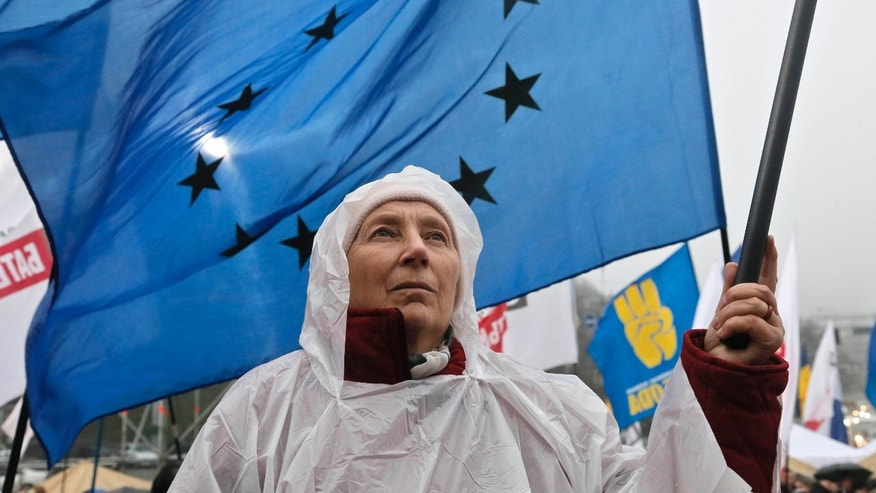An activist holds a European Union flag during a rally at European Square in Kiev, Ukraine, Monday, Nov. 25, 2013. Demonstators rallied in the center of Kiev to demand that the Ukrainian government reverse course and sign a landmark agreement with the European Union in defiance of Russia. (AP Photo/Efrem Lukatsky)