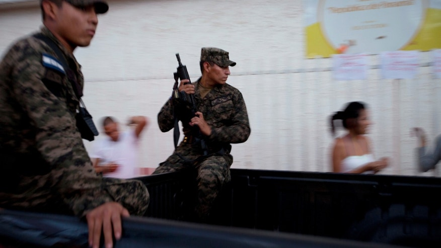 Soldiers patrol outside a voting station after polls closed for general elections in Tegucigalpa, Honduras, Sunday, Nov. 24, 2013. Hondurans cast ballots for a new president Sunday in a country reeling from violence, poverty and the legacy of a 2009 coup, and if opinion polls were accurate, the vote could fail to produce a clear winner. (AP Photo/Moises Castillo)