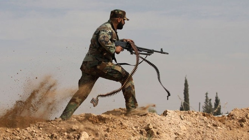 Nov. 22, 2013: In this file photo, a Shiite fighter clashes with members of the Sunni-dominated Free Syrian Army rebel in the town of Hatita, in the countryside of Damascus, Syria.