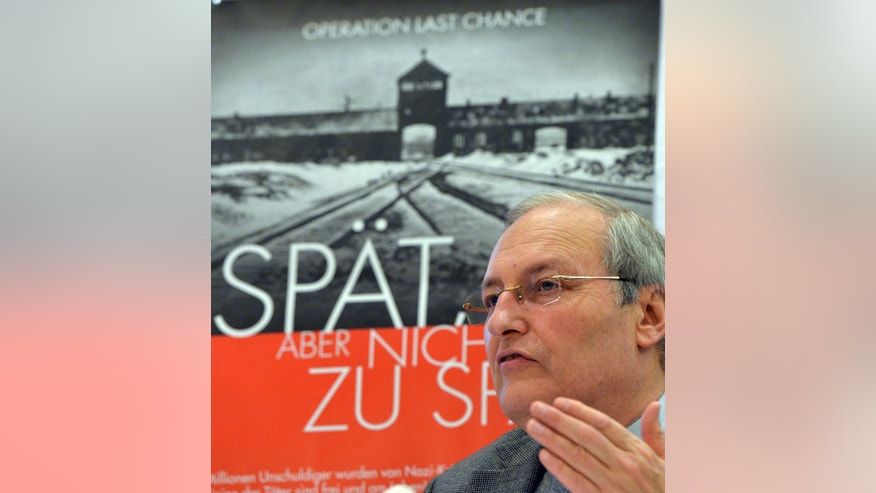 "Efraim Zuroff, the top Nazi-hunter of Simon Wiesenthal Center, speaks during a news conference in Munich, Germany, Monday, Nov. 25, 2013. Zuroff launched the ""Operation Last Chance II"", a poster campaign to bring individuals to justice who were involved in the mass murder of Jews during the Holocaust. The poster in background reads 'late but not too late'.  (AP Photo/Kerstin Joensson)"