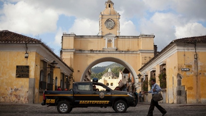 In this Nov. 14, 2013 photo, police patrol along a main street close to the Santa Catalina convent in Antigua, Guatemala. Vehicle and home burglaries are up, and once-reliable public services such as water and trash collection have been left unattended across whole blocks.  (AP Photo/Luis Soto)
