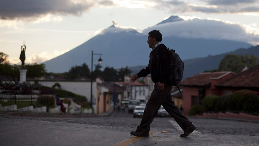 In this Nov. 14, 2013 photo, a man walks over the Matasanos bridge, the main entrance to Antigua, Guatemala. Behind is the Fire volcano, left, and the Acatenango volcano. With its cobblestone streets and colonial-era churches and plazas, the picturesque city of Antigua has long been Guatemala's top tourist destination and an oasis away from the crime and chaos consuming the rest of the tiny Central American country. (AP Photo/Luis Soto)