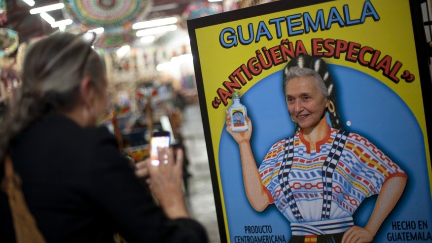 In this Nov. 14, 2013 photo, a tourist pose for her friend behind a cut-out sign advertising a local beverage at the market in Antigua, Guatemala. Antigua attracts tourists from all over the world with its crumbling colonial charm, and an elaborate procession that winds through the city's streets around Lent. (AP Photo/Luis Soto)