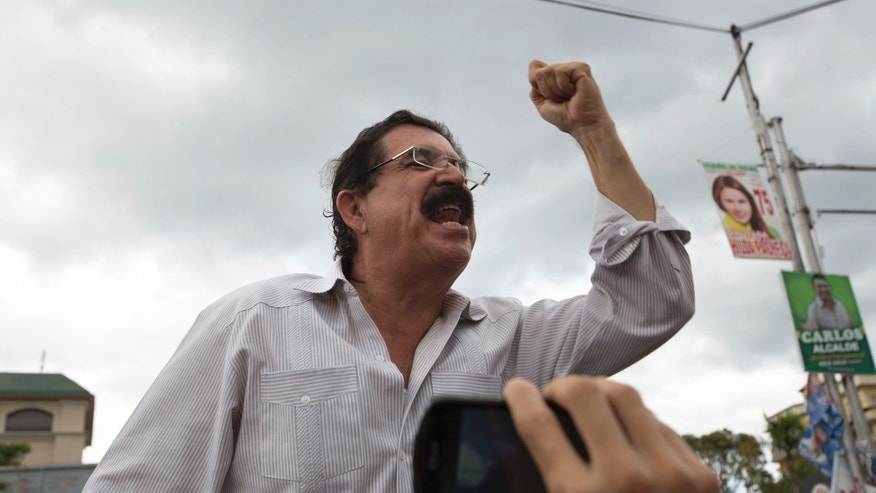 Ousted President Manuel Zelaya, general secretary of the Free Party whose presidential candidate is his wife Xiomara Castro, greets supporters as he leaves a hotel after giving a press conference in Tegucigalpa, Honduras, Monday, Nov. 25, 2013. The two top presidential candidates continued to claim victory Monday in a hotly contested presidential race, as Hondurans awaited final results. (AP Photo/Moises Castillo)
