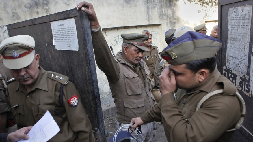 "Indian police guard the entrance of a court during the proceedings of the trial of a double murder case of Aarushi and Hemraj in Ghaziabad, India, Monday, Nov. 25, 2013. Rajesh Talwar and his wife Nupur have been convicted of killing their 14-year-old daughter Aarushi and their housekeeper Hemraj in 2008, by the court. The two married dentists will be sentenced Tuesday. They could face the death penalty. In a statement, they said they were ""hurt and anguished"" by the verdict and would appeal. (AP Photo/Tsering Topgyal)"