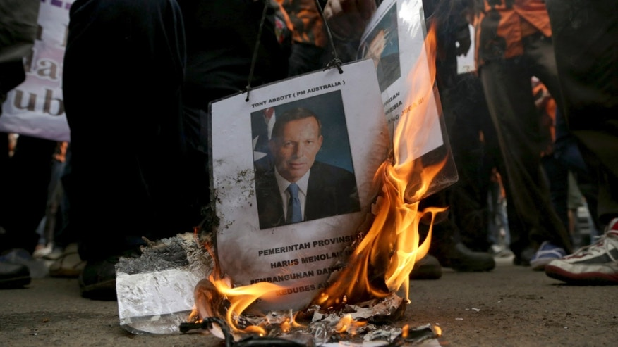 Protesters burn a poster of Australian Prime Minister Tony Abbott during a demonstration outside Australian Embassy in Jakarta, Indonesia. Tuesday, Nov. 26. 2013. Indonesia downgraded relations and suspended cooperation on people-smuggling after reports of Australian tapping the phones of President Susilo Bambang Yudhoyono, his wife and eight Indonesian ministers and officials in 2009. (AP Photo/Achmad Ibrahim)