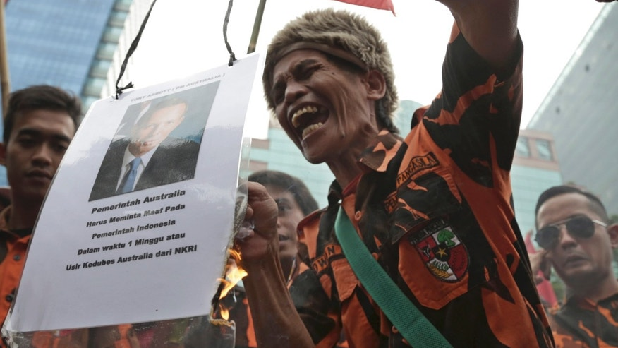 A protester holds a burning poster of Australian Prime Minister Tony Abbott as he shouts slogans during a demonstration outside Australian Embassy in Jakarta, Indonesia. Tuesday, Nov. 26. 2013. Indonesia downgraded relations with Australia and suspended cooperation on people-smuggling after reports of Australian tapping the phones of President Susilo Bambang Yudhoyono, his wife and eight Indonesian ministers and officials in 2009. (AP Photo/Achmad Ibrahim)