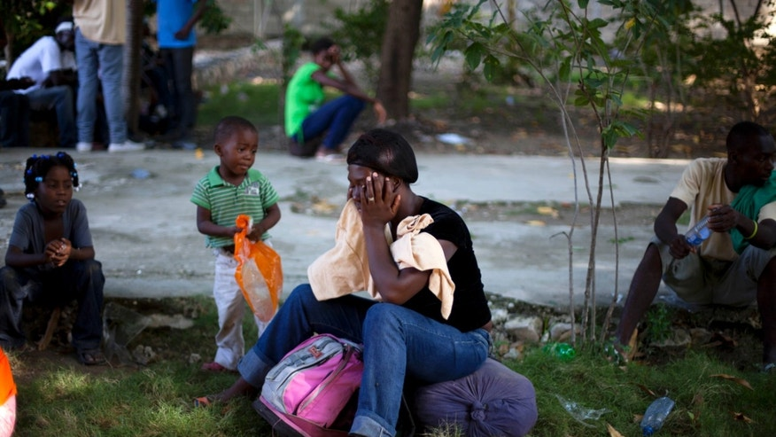A woman and her children wait at a shelter to be taken to their hometown together with other Haitians after being deported by Dominican Republic authorities, in Croix-des-Bouquets, Haiti, Sunday Nov. 24, 2013. Dominican authorities expelled 244 Haitians after an elderly Dominican couple was slain in an apparent burglary near the border between the two countries and an angry mob retaliated by killing a Haitian man, Rev. Antoine Lissaint of Haiti's Jesuit Refugee and Migrant Organization said Sunday.(AP Photo/Dieu Nalio Chery)