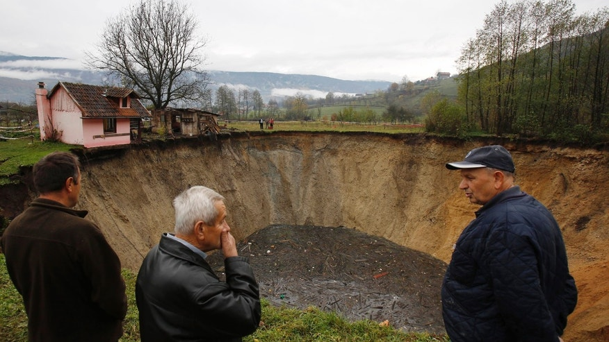 "In this Thursday, Nov. 21, 2013 photo, people gather around a huge sinkhole in the village of Sanica, Bosnia. Only weeks ago, the spot was a pond full of fish and floating green algae, lined with old willow and plum trees, and a grass field where cattle used to peacefully graze. The vanishing pond was some 20-meters in diameter and about 10-meters deep. Now, the ""abyss"" as the villagers named the dry sinkhole, is some 50-meters wide and 30-meters deep. Scientists say it is not an uncommon occurrence that ponds and small lakes disappear. They say it could be caused by drying underground waters, or changes in soil drainage due to agricultural irrigation. (AP Photo/Amel Emric)"