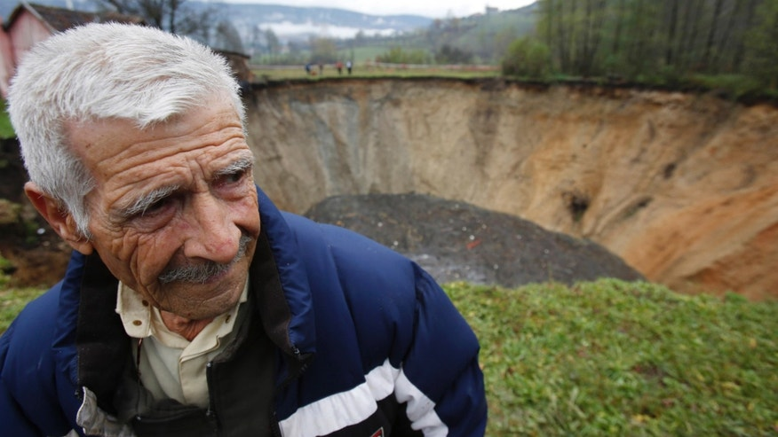 "In this Thursday, Nov. 21, 2013 photo, Ekrem Keramovic stands near a huge sinkhole in the village of Sanica, Bosnia. Only weeks ago, the spot was a pond full of fish and floating green algae, lined with old willow and plum trees, and a grass field where cattle used to peacefully graze. The vanishing pond was some 20-meters in diameter and about 10-meters deep. Now, the ""abyss,"" as the villagers named the dry sinkhole, is some 50-meters wide and 30-meters deep. Scientists say it is not an uncommon occurrence that ponds and small lakes disappear. They say it could be caused by drying underground waters, or changes in soil drainage due to agricultural irrigation. (AP Photo/Amel Emric)"