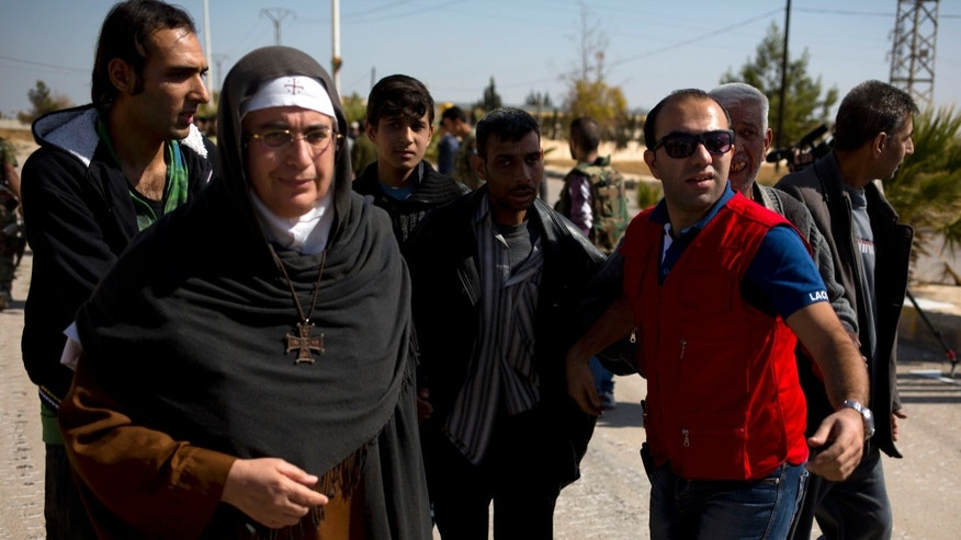 In this Oct. 29, 2013 photo, Mother Superior Agnes-Mariam Of The Cross walks with people fleeing the rebel held suburb of Moadamiyeh to the government held territory in Damascus, Syria. Amid Syria's brutal civil war, a nun has emerged as an unlikely power broker and figure of controversy. Mother Superior Agnes-Mariam of the Cross has thrust herself into the role of go-between and publicist, arranging cease-fires, organizing pro-government media trips and conducting speaking tours as perhaps the country's most prominent critic of the uprising against President Bashar Assad. (AP Photo/Dusan Vranic)