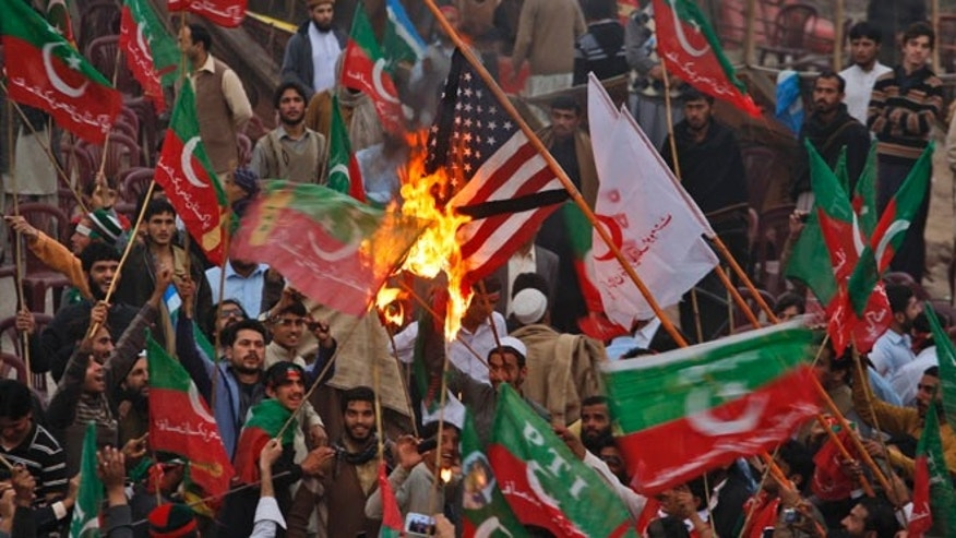 Nov. 23, 2013: Supporters of Pakistan's Tehreek-e-Insaf party, headed by cricketer-turned politician Imran Khan, wave their party's flag while burning a representation of a U.S. flag during a protest against U.S. drone strikes in Pakistan, in Peshawar, Pakistan.