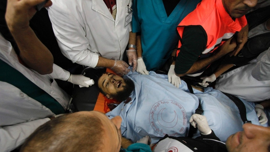 Medics stand around the body of Mohammad Nairoukh who was killed Tuesday by Israeli security forces in the West Bank village of Yatta, south of Hebron, Wednesday, Nov. 27, 2013. Israeli security forces shot and killed three suspected militants in a West Bank raid on Tuesday aimed at thwarting an attack on Israeli targets, the military and police said. (AP Photo/Nasser Shiyoukhi)