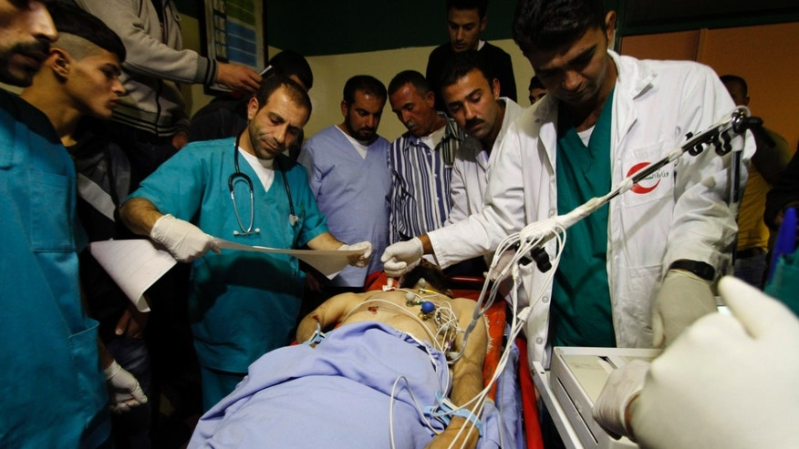 Doctors examine the body of Mohammad Nairoukh who was killed Tuesday by Israeli security forces in the West Bank village of Yatta,  south of Hebron, Wednesday, Nov. 27, 2013. Israeli security forces shot and killed three suspected militants in a West Bank raid on Tuesday aimed at thwarting an attack on Israeli targets, the military and police said. (AP Photo/Nasser Shiyoukhi)