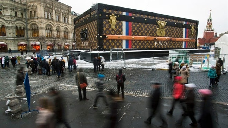 Nov. 27, 2013: Tourists and visitors pass by a two-story Louis Vuitton suitcase erected at the Red Square in Moscow, Russia.