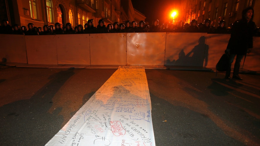 Part of a  500-meter-long signed petition addressed to Ukraine's President Viktor Yanukovych laying on the ground not far from the presidential palace in the centre of Kiev, Ukraine, Wednesday Nov. 27, 2013. Thousands of people on Wednesday kept up their nearly week-long protest against the Ukrainian government's decision to ditch an agreement with the European Union in favor of closer ties with Russia, but officials showed no signs of relenting to their demands. (AP Photo/Sergei Grits)