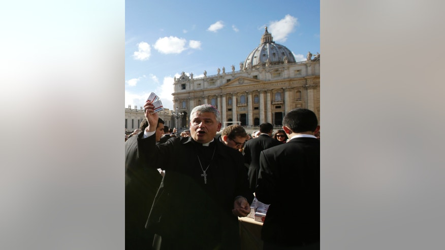 In this photo taken on Sunday, Nov. 17, 2013, Vatican Almoner, Archbishop Konrad Krajewski distributes rosaries in boxes designed to resemble a packet of pills, outside St. Peter's Basilica, at the Vatican. The existence of the Vatican Almoner dates back centuries: It is mentioned in a papal bull from the 13th-century Pope Innocent III, and Pope Gregory X, who ruled from 1271-1276, organized it into an official Holy See office for papal charity. Up until Krajewski came along, the almoner was typically an aging Vatican diplomat who was serving his final years before being allowed to retire at age 75. Francis changed all that, tapping the 50-year-old Pole to be a more vigorous, hands-on extension of himself. The almoner's duties are two-fold: carrying out acts of charity, and raising the money to fund them. (AP Photo/Gregorio Borgia)