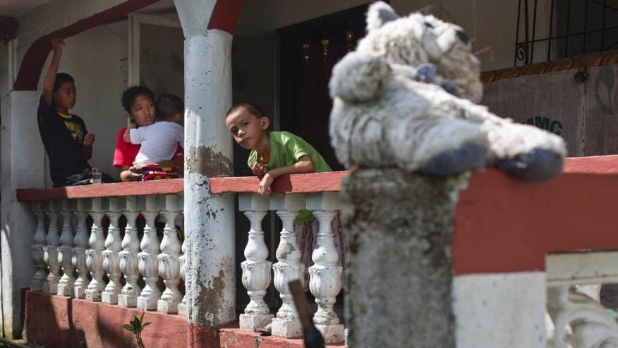 In this Nov. 21, 2013 photo, four siblings who were orphaned by Typhoon Haiyan, stand on the porch of a relative's home in Burauen, the Philippines. From left to right are Richard Chris Negru, 12, Shylyny Therese Negru, 15,  Rainier Aaron Dacuno, 3, and Richard Aaron Dacuno, 6.  The children are among an unknown number of children in the eastern Philippines who lost their parents to the massive Nov. 8 storm. (AP Photo/David Guttenfelder)