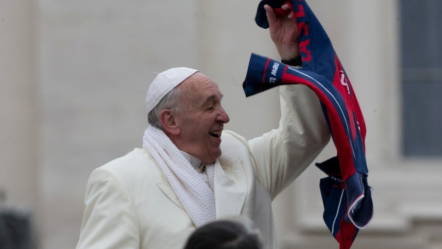 Pope Francis grabs a shirt thrown to him by faithful as he leaves at the end of his weekly general audience in St. Peter's Square at the Vatican, Wednesday, Nov. 27, 2013. A chilly Pope Francis has cheered the thousands of pilgrims who braved a cold snap belting Italy to attend his weekly general audience, saying they were courageous to come out. (AP Photo/Alessandra Tarantino)