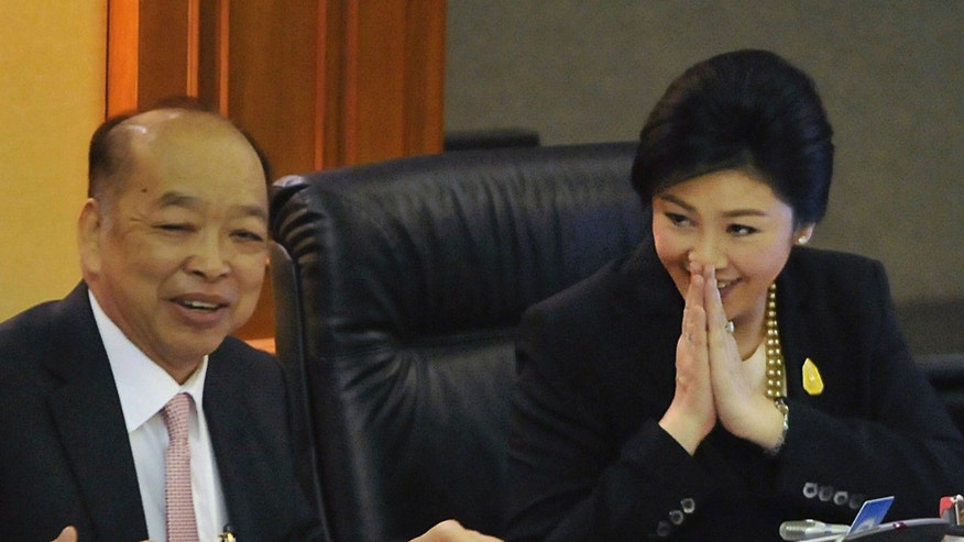 "Thailand Prime Minister Yingluck Shinawatra, right, along with Foreign Minister Surapong Tovichakchaikul, left, gives a Thai traditional way of greeting ""wai"" after the debate on a no-confidence vote at the parliament in Bangkok, Thailand, Thursday, Nov. 28, 2013. Thailand's embattled prime minister easily survived a no-confidence vote in parliament. Lawmakers in Bangkok voted 297 to 134 Thursday against unseating Yingluck Shinawatra, who faces protests by opponents who want to bring down her government.(AP Photo)"