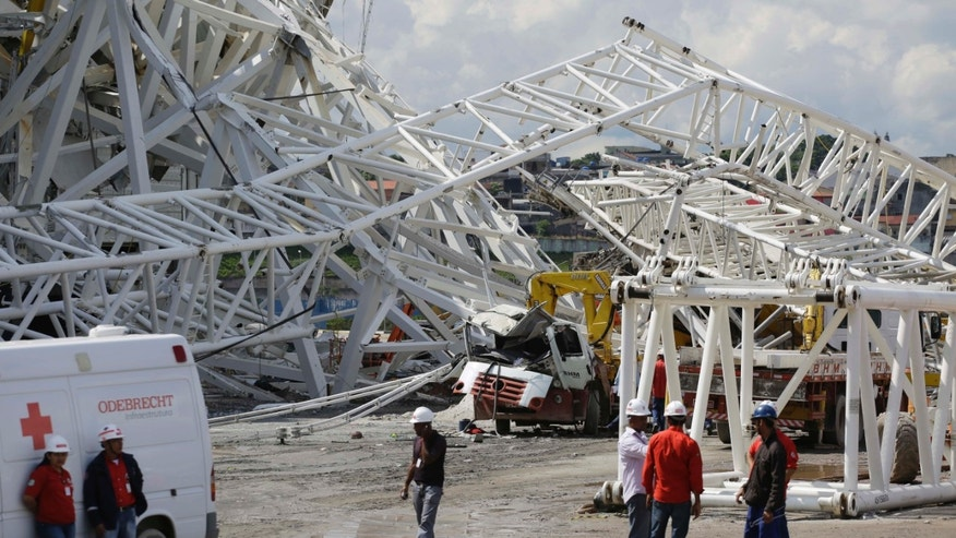 People stand near a metal structure that buckled on part of the Itaquerao Stadium in Sao Paulo, Brazil, Wednesday, Nov. 27, 2013. Part of the stadium that will host the 2014 World Cup opener in Brazil collapsed on Wednesday, causing significant damage and killing at least two people, authorities said. (AP Photo/Nelson Antoine)