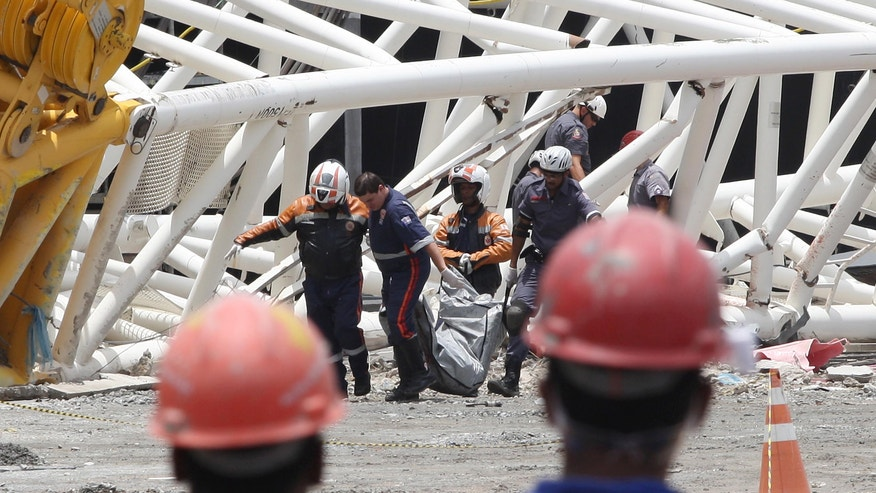Firefighters recover the body of a worker who was killed when a part of the Itaquerao stadium collapsed, in Sao Paulo, Brazil, Wednesday, Nov. 27, 2013.  Part of the stadium that will host the 2014 World Cup opener in Brazil collapsed on Wednesday, killing two workers and raising urgent new concerns whether the country will be ready for soccer's signature event. (AP Photo/ Eduardo Viana/Lancepress)