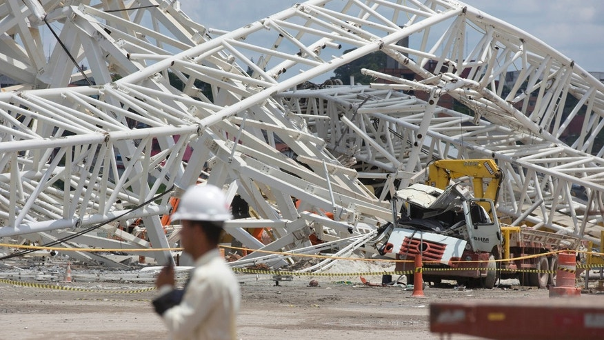 A collapsed metal structure sits on the ground at the Arena Corinthians, known locally as the Itaquerao, in Sao Paulo, Brazil, Thursday, Nov. 28, 2013. The accident that resulted in the death of at least two workers, occurred when a construction crane crashed into a 500-ton metal structure that in turn cut through the outer walls of the venue, destroying rows of seats and slamming into a massive LED panel that runs across the stadium's facade. The stadium is slated to host the 2014 World Cup opener.  (AP Photo/Andre Penner)