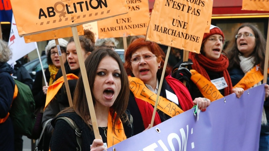 People demonstrate against prostitution outside the parliament in Paris, Friday Nov. 29, 2013. France's government is pushing one of Europe's toughest laws against prostitution and sex trafficking, with other countries are watching closely. Advocates hope that a draft French law will help change long-held attitudes toward the world's oldest profession — by punishing the customer and protecting the prostitute. Debates start this Friday. Placard at center reads: Our body is not  merchandise. (AP Photo/Francois Mori)