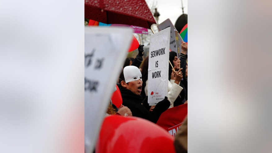 A French sex worker demonstrates outside the National Assembly in Paris, Friday, Nov. 29, 2013. Protestors gather against a government plan to penalize clients caught in the act of soliciting a prostitute. (AP Photo/Christophe Ena)