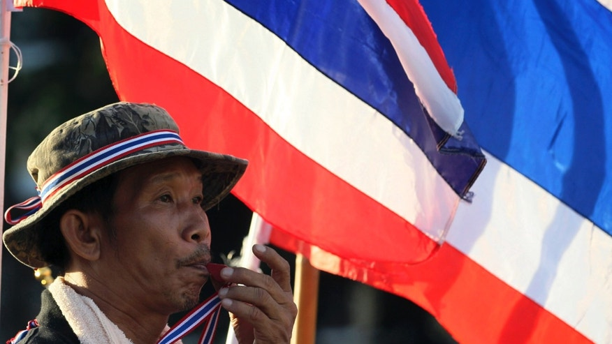 An anti-government protester blows a whistle in front of Thai National flags during rally at the Democracy Monument in Bangkok, Thailand, Friday, Nov. 29, 2013. Thailand's prime minister begged protesters Thursday to call off their sustained anti-government demonstrations and negotiate an end to the nation's latest crisis.(AP Photo/Sakchai Lalit)