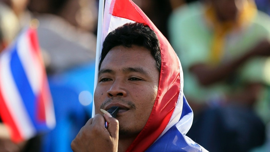 An anti-government protester blows a whistle during a rally at the Democracy Monument in Bangkok, Thailand, Friday, Nov. 29, 2013. Thailand's prime minister begged protesters Thursday to call off their sustained anti-government demonstrations and negotiate an end to the nation's latest crisis.(AP Photo/Sakchai Lalit)