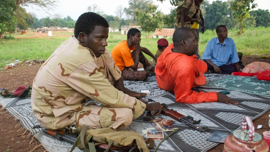 "In this photo taken Monday, Nov. 25, 2013, armed Muslim fighters from the former Seleka rebel coalition sit in the town of Bouca in the Central African Republic. France's foreign minister has warned that its former colony in central Africa is ""on the verge of genocide"" as attacks mount across the country's remote northwest between the mostly Muslim fighters of the Seleka rebel coalition who ousted the president in March, and ""anti-balaka"" Christian militias that have emerged to defend towns and in some cases attack Muslim civilian communities. (AP Photo/Florence Richard)"