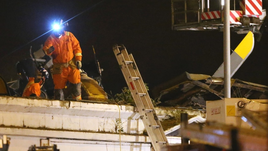 Firefighters and rescue workers inspect the damage on the roof of the building at the site of a helicopter crash, in Glasgow early Saturday Nov. 30, 2013. The police helicopter crashed late Friday night into the roof of a popular pub in Glasgow, Scotland, leaving the building littered with debris and emergency crews scrambling to the scene. (AP Photo /Andrew Milligan, PA) UNITED KINGDOM OUT, NO SALES, NO ARCHIVES