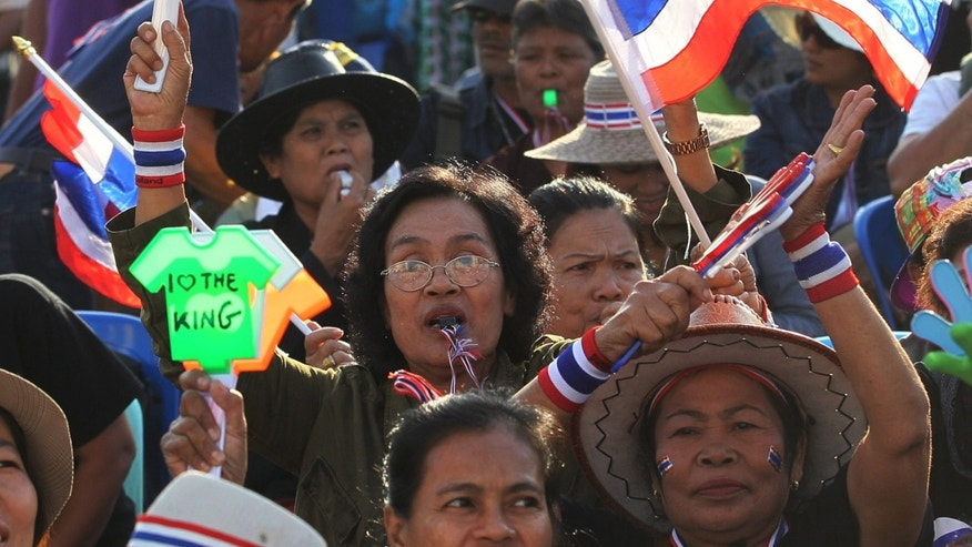 Anti-government protesters wave Thai National flags and clapping tool during rally at the Democracy Monument in Bangkok, Thailand, Saturday, Nov. 30, 2013. Protesters forced their way onto the grounds of Thailand's army headquarters on Friday, asking the military to support their increasingly aggressive campaign to topple Prime Minister Yingluck Shinawatra. The army insisted it will not take sides in the dispute.(AP Photo/Sakchai Lalit)
