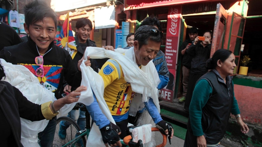 Rinpo Yak, center, a 42-year-old Tibetan exile living in the U.S., is greeted with ceremonial scarves by exile Tibetans as he reaches the headquarters of the Tibetan government-in-exile and home to the Dalai Lama in Dharmsala, India, Saturday, Nov. 30, 2013. Yak started his bike journey from Brussels, traveling through 13 European countries and Japan to spread awareness about the Tibetan issue before reaching India. (AP Photo/Ashwini Bhatia)