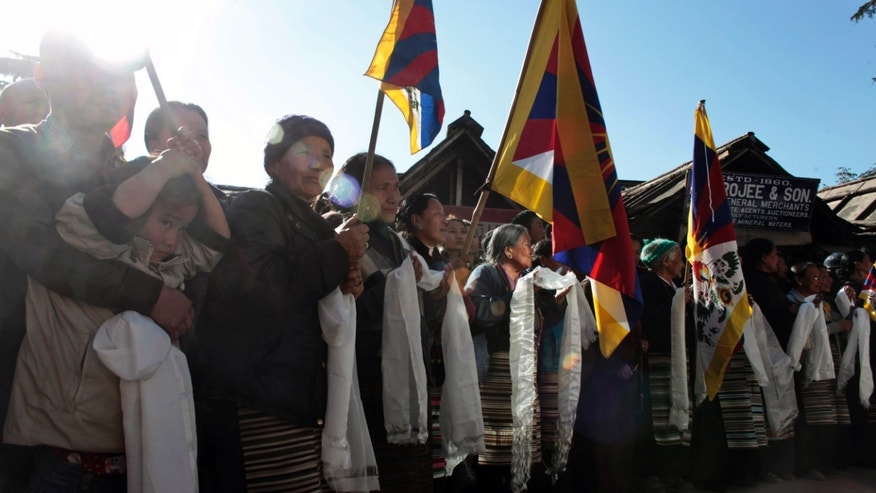 Exiled Tibetans wait with flags and ceremonial scarves to welcome Rinpo Yak, a 42-year-old Tibetan exile living in the U.S., as he reaches the headquarters of the Tibetan government-in-exile and home to the Dalai Lama in Dharmsala, India, Saturday, Nov. 30, 2013. Yak started his bike journey from Brussels, traveling through 13 European countries and Japan to spread awareness about the Tibetan issue before reaching India. (AP Photo/Ashwini Bhatia)