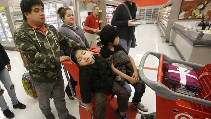 Cesar and Marie Cruz push their sons Sevier, 3, foreground, and Trinni, 8, in a shopping cart at a Target store in Colma, Calif., Thanksgiving Day, Thursday, Nov. 28, 2013. Instead of waiting for Black Friday, which is typically the year's biggest shopping day, more than a dozen major retailers opened on Thanksgiving day this year. (AP Photo/Jeff Chiu)