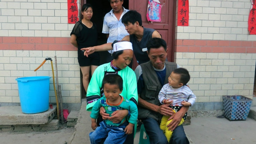 In this photo taken Tuesday, July 16, 2013, Mu Zhengwu, center, gathers his family for a group photo that includes his oldest brother, Mu Hongzhong, background center; their father, Mu Qingdeng, front right; and mother, Chai Guixian, left seated, at their rural home in Anshun in southern China's Guizhou province. Mu, born into a poor rural family in China's most impoverished province, beats all odds to attend a prestigious Beijing Law School. (AP Photo/Didi Tang)