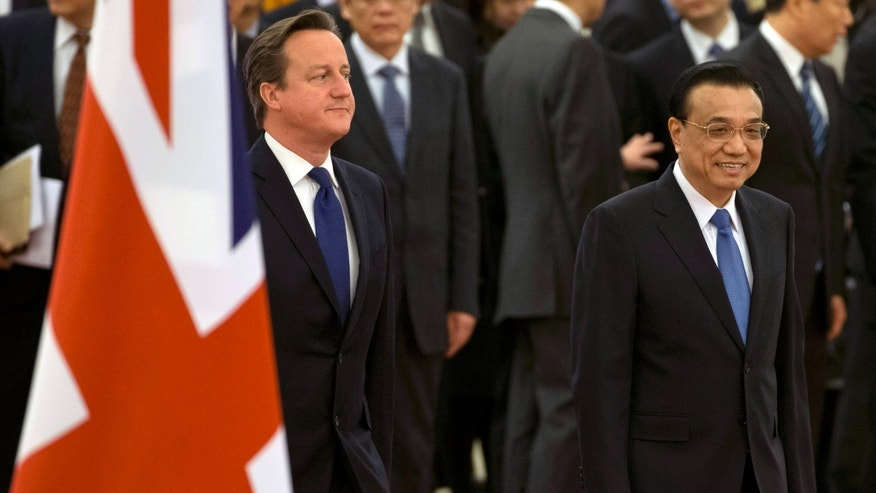 British Prime Minister David Cameron, left, walks with Chinese Premier Li Keqiang past the British flag as they arrive for a welcome ceremony at the Great Hall of the People in Beijing, China, Monday, Dec. 2, 2013. (AP Photo/Ng Han Guan)