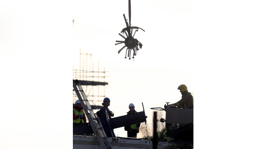 Scottish Fire and Rescue services look on at a section of the helicopter being lifted from the scene Sunday, Dec. 1, 2013, following the helicopter crash at the Clutha Bar in Glasgow, Scotland. Scottish emergency workers were sifting through wreckage Saturday for survivors of a police helicopter crash onto a crowded Glasgow pub that has killed at least eight people and injured more than two dozen. The Clutha pub, near the banks of the River Clyde, was packed Friday night and a ska band was in full swing when the chopper slammed through the roof. The number of fatalities is expected to rise, officials said. (AP Photo/Scott Heppell)